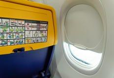 瑞安航空公司航空器位子以由窗口的安全信息 免版税库存图片