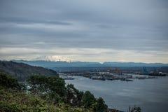 瑞尼尔山冠上了与与下面塔科马港的云彩  免版税库存照片