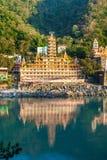 瑞诗凯诗,印度- Noveber 2012年:从另一家甘加银行的泰罗的Manzil寺庙视图有镜象反射的在水中 免版税库存照片