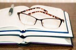 玻璃、书和笔记本在桌上浮出水面 免版税库存照片
