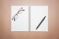 玻璃、笔记本和笔在一张包装纸 免版税库存图片