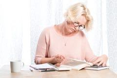 玻璃候宰栏的妇女转动书页 免版税库存照片
