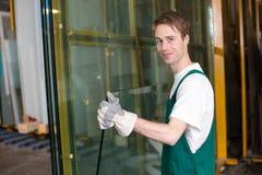 玻璃剪裁工在处理玻璃的车间 免版税库存图片