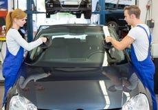 玻璃剪裁工在石头切削以后替换挡风玻璃或挡风玻璃在汽车 免版税库存图片