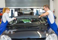 玻璃剪裁工在石头切削以后替换挡风玻璃或挡风玻璃在汽车 免版税库存照片