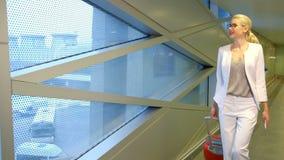 玻璃和一件白色礼服的美丽的金发碧眼的女人带着手提箱去 股票视频