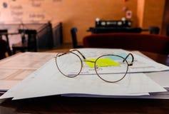 玻璃和书在木桌上 库存图片