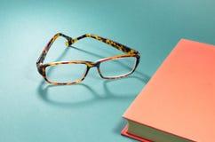 玻璃和书在桌上 免版税库存照片