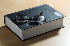 玻璃和厚实的书在精装书 免版税库存图片