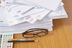 玻璃和文书工作和计算器有笔和铅笔的 免版税库存图片