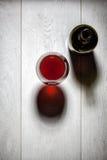 玻璃和瓶与黄柏的红葡萄酒在桌上 库存图片
