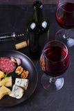 玻璃和瓶红葡萄酒,乳酪,面包,大蒜,坚果,在灰色石纹理背景的蒜味咸腊肠 在视图之上 库存图片