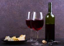 玻璃和瓶红葡萄酒,乳酪,面包,大蒜,坚果,在灰色石纹理背景的蒜味咸腊肠 库存图片