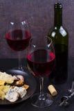 玻璃和瓶红葡萄酒,乳酪,面包,大蒜,坚果,在灰色石纹理背景的蒜味咸腊肠 免版税库存图片