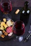 玻璃和瓶红葡萄酒,乳酪,面包,大蒜,坚果,在灰色石纹理背景的蒜味咸腊肠 免版税库存照片