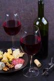 玻璃和瓶红葡萄酒,乳酪,面包,大蒜,坚果,在灰色石纹理背景的蒜味咸腊肠 库存照片