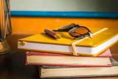 玻璃和笔在书 免版税库存图片