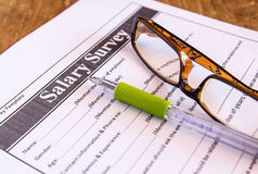 玻璃和笔在薪金调查从 免版税库存照片