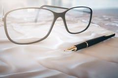 玻璃和笔 库存照片