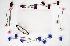 玻璃和纸与花圈框架从野花 免版税库存照片