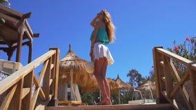 玻璃和裙子的俏丽的女孩在步在慢动作站立并且恭敬地保留 影视素材