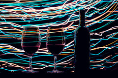 玻璃和酒瓶在黑背景和足迹 免版税库存图片