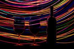 玻璃和酒瓶在黑背景和足迹 免版税库存照片