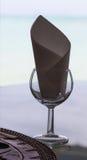 玻璃和餐巾剪影在服务的桌上在餐馆 免版税库存照片