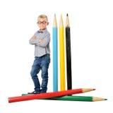 玻璃和bowtie摆在的愉快的男孩全长与一支巨大的铅笔 培训的概念 查出在白色 免版税库存照片