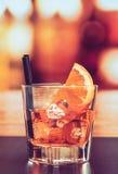 玻璃喷开胃酒与橙色切片和冰块的aperol鸡尾酒在酒吧桌,葡萄酒大气背景上 免版税库存图片