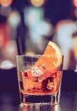 玻璃喷开胃酒与橙色切片和冰块的aperol鸡尾酒在酒吧桌,葡萄酒大气背景上 免版税图库摄影
