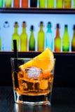 玻璃喷开胃酒与橙色切片和冰块的aperol鸡尾酒在酒吧桌,迪斯科休息室酒吧大气背景上 免版税库存照片