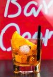 玻璃喷开胃酒与橙色切片和冰块的aperol鸡尾酒在酒吧桌,迪斯科大气背景上 库存照片