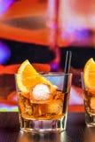 玻璃喷开胃酒与橙色切片和冰块的aperol鸡尾酒在酒吧桌,颜色流行音乐大气背景上 免版税库存图片