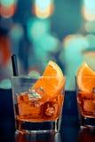 玻璃喷开胃酒与橙色切片的aperol鸡尾酒,并且在酒吧的冰块制表,流行样式大气背景 免版税图库摄影