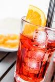玻璃在切片桔子附近板材喷开胃酒与橙色切片和冰块的aperol鸡尾酒 免版税库存照片