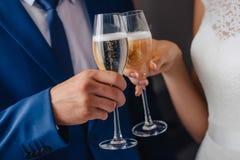玻璃在新娘和新郎的手上 免版税库存照片