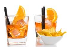 玻璃在炸玉米饼芯片附近喷开胃酒与橙色切片和冰块的aperol鸡尾酒 免版税库存图片
