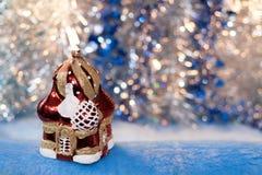 玻璃在金黄蓝色bokeh backgr的圣诞节玩具红白的寺庙 库存照片