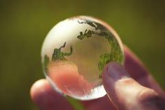 玻璃地球宏观照片在人的手上 免版税图库摄影