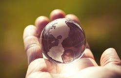 玻璃地球宏观照片在人的手上 免版税库存图片