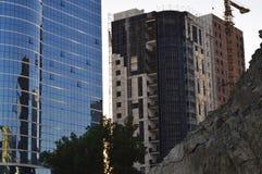 玻璃塔和另一个大厦被修建,修造的起重机 库存图片