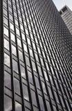 玻璃大厦,摩天大楼在中间地区,在有反射和蓝天的曼哈顿 免版税图库摄影
