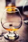 玻璃威士忌酒科涅克白兰地白兰地酒或兰姆酒 二分之一充分的杯木表面上的科涅克白兰地 库存照片