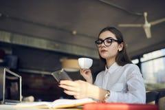 玻璃工作的女孩使用现代技术和释放在现代coworking的空间的无线连接 免版税库存照片