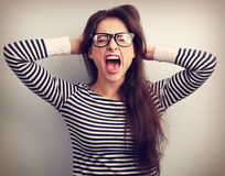 玻璃强尖叫的恼怒的年轻女商人与狂放 免版税库存照片