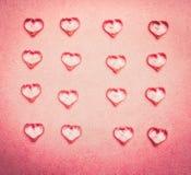 玻璃心脏平的位置在桃红色背景的 免版税库存照片