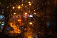 玻璃有雨与bokeh的下落背景在夜 免版税库存照片