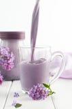 玻璃杯子用在淡紫色花附近的倾吐的越桔奶昔 库存照片