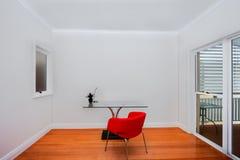玻璃桌和一把红色椅子 图库摄影